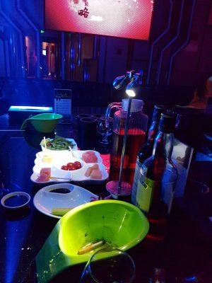 テーブルの上にある白いお皿、上から順に、枝豆、フルーツ、キュウリ