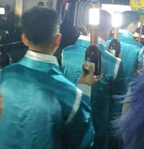お酒に電球を装着し、それを手にもって一列で行進するスタッフ